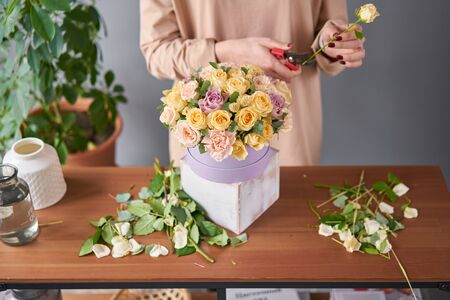 Florist woman creates flower arrangement in a round box. Beautiful bouquet of mixed flowers. Floral shop concept . Handsome fresh bunch. Flowers delivery Stock fotó