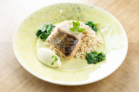 Roasted Pike perch with spelt and Polish sauce. Dish decorated with a spinach. Restaurant menu