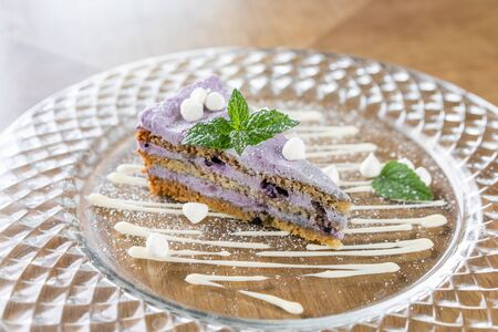 Blueberry sponge cake decorated with meringue and mint leaves. Breakfast in the cafe, morning coffee. on wooden table. Restaurant menu Banco de Imagens