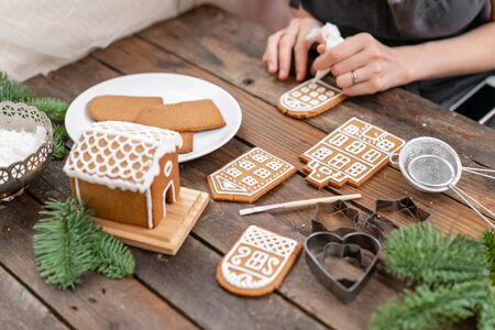 Christmas homemade gingerbread cookies on wooden table. Icing of Christmas bakery. closeup, copy space. Blank biscuit gingerbread house, ready to decorate Reklamní fotografie