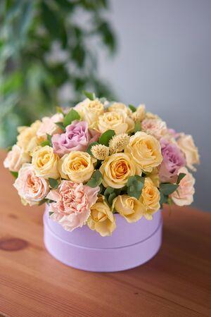 Floristfrau schafft Blumenarrangement in einer runden Schachtel. Schöner Strauß gemischter Blumen. Blumenladenkonzept. Hübscher frischer Haufen.