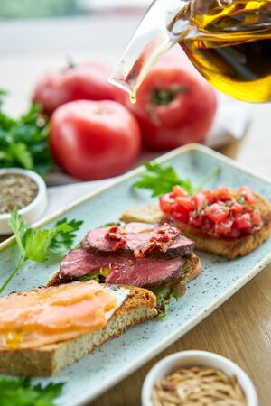 Bruschetta with beef, tomatoes and salmon.. Variety of dishes on the table. Various snacks and antipasti on the table. Restaurant menu. Italian cuisine