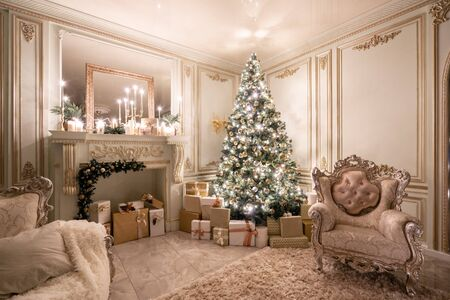 Christmas evening in the light of candles and garlands. Classic luxurious apartments with decorated christmas tree and presents. Living with fireplace, columns and stucco.