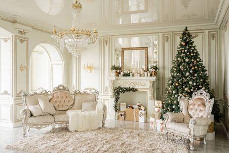Weihnachtsmorgen. Klassische Luxusappartements mit geschmücktem Weihnachtsbaum und Geschenken. Wohnen mit Kamin, Säulen und Stuck. Standard-Bild