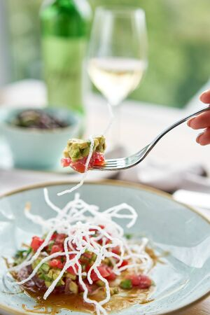 Closeup fork with pieces of food. Woman eating tartar in the restaurant. Variety of dishes on the table. Italian cuisine