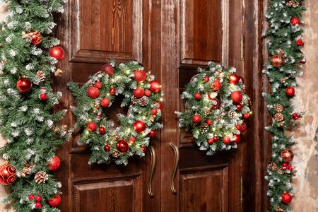House entrance decorated for holidays. Christmas decoration. Two wreaths and garland of fir tree branches. Large wooden door.