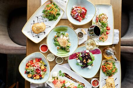 Ensalada griega tradicional con verduras frescas, queso feta y aceitunas. Mesa de madera en restaurante.