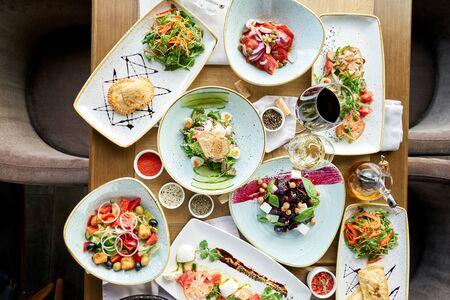Insalata greca tradizionale con verdure fresche, formaggio feta e olive. Tavolo in legno in ristorante.