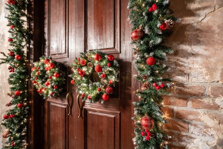 House entrance decorated for holidays. Christmas decoration. Two wreaths and garland of fir tree branches. Large wooden door