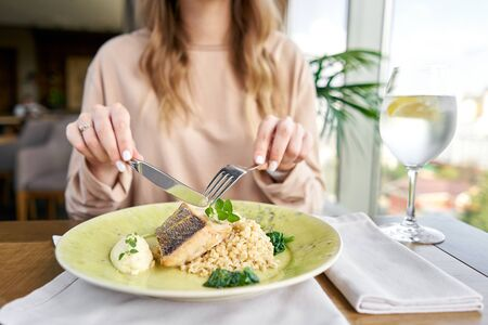 Roasted Pike perch with spelt and Polish sauce. Lunch in a restaurant, a woman eats delicious and healthy food. Dish decorated with a spinach. Restaurant menu