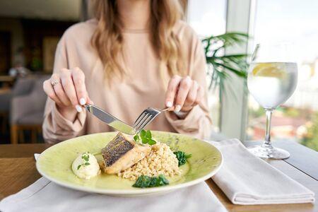 Sandre rôti à l'épeautre et sauce polonaise. Déjeuner dans un restaurant, une femme mange des aliments délicieux et sains. Plat décoré d'épinards. Le menu du restaurant Banque d'images
