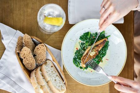 Salmon steak fillet with grainy mustard and spinach. Lunch in a restaurant, a woman eats delicious and healthy food. Restaurant menu, a series of photos of different dishes Stock Photo