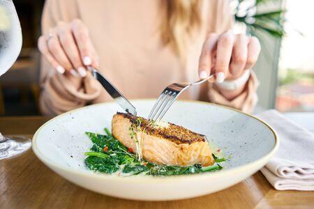 Lachssteakfilet mit körnigem Senf und Spinat. Mittagessen in einem Restaurant, eine Frau isst leckeres und gesundes Essen. Speisekarte des Restaurants, eine Reihe von Fotos verschiedener Gerichte