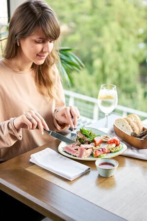 Lunch in a restaurant, a woman eats Medium rare tuna with lettuce and hot sauce. Restaurant menu