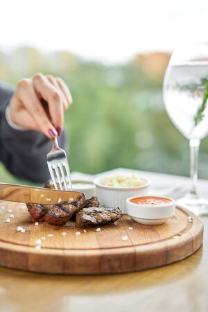 Lunch in a restaurant, a woman cuts Pieces of liver cooked on the grill. Serving on a wooden Board. Barbecue restaurant menu, a series of photos of different meats.