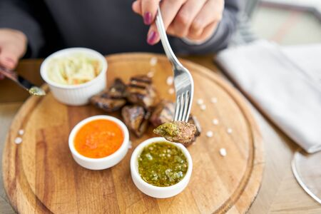 Lunch in a restaurant, a woman eats Pieces of liver cooked on the grill. Serving on a wooden Board. Barbecue restaurant menu, a series of photos of different meats.