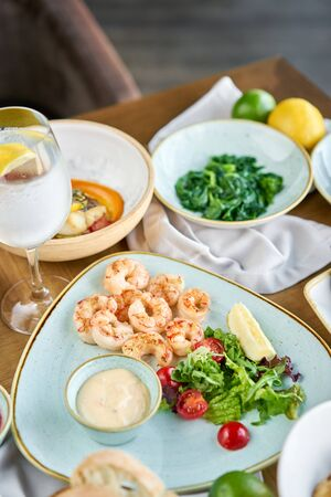 Dish shrimp with arugula and lemon. BBQ seafood. Restaurant menu. Variety of dishes on the table. Restaurant menu. Zdjęcie Seryjne