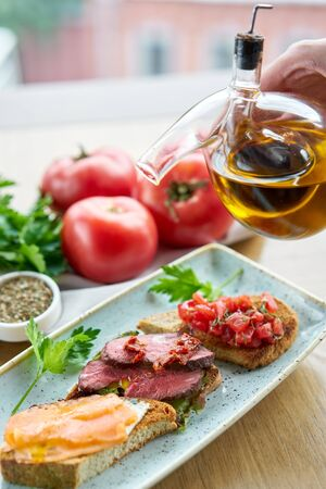 Bruschetta with beef, tomatoes and salmon.. Variety of dishes on the table. Various snacks and antipasti on the table. Restaurant menu. Italian cuisine Stock Photo