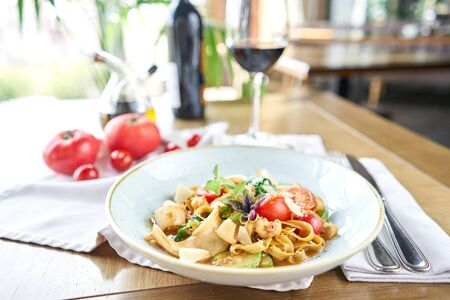 Italian pasta with seafood and tomato sauce. Pasta Gamberini. Close-up tagliatelle wind it around a fork with a spoon. Parmesan cheese Zdjęcie Seryjne