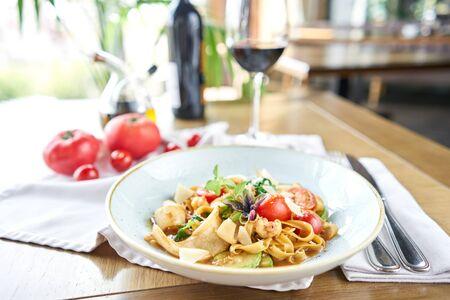 Pasta italiana con marisco y salsa de tomate. Pasta Gamberini. Los tagliatelle de primer plano se enrollan alrededor de un tenedor con una cuchara. queso parmesano Foto de archivo