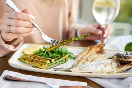 Lunch in a restaurant, a woman eats roasted dorado fish with grilled asparagus. Dish decorated with a slice of lemon. Restaurant menu