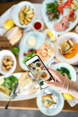 A blogger takes a photo on a smartphone for social networks. Table with Plates seafood BBQ with garnish. Variety of dishes on the table. Restaurant menu. Stock Photo