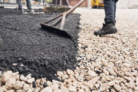 Laying new asphalt, covering the pit, on the rubble. Workers carry in shovels and using asphalt lute for smooth, hot asphalt. Archivio Fotografico
