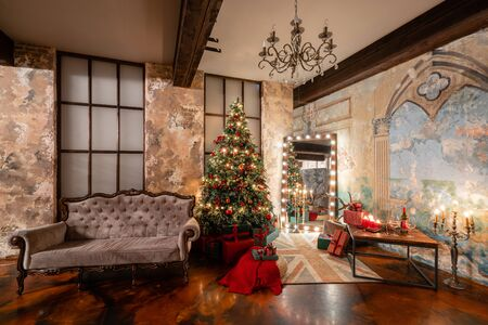 Winter home decor. Christmas in loft interior against brick wall. gifts under the tree. star lamp with light bulbs. Mirror garlands 스톡 콘텐츠