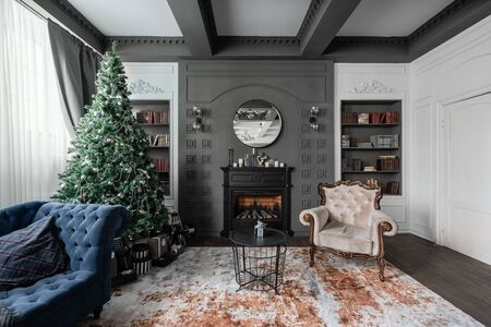 Christmas morning. Classic apartments with study and library a fireplace, decorated tree, sofa, large windows and chandelier.