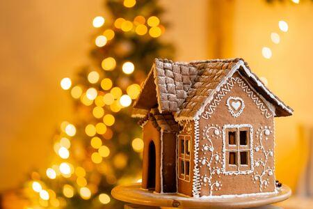 Lebkuchenhaus, Konzepturlaub von Weihnachten und Frohes neues Jahr. Defokussierte Lichter des Weihnachtsbaums. Morgen im hellen Wohnzimmer. Urlaubsstimmung.