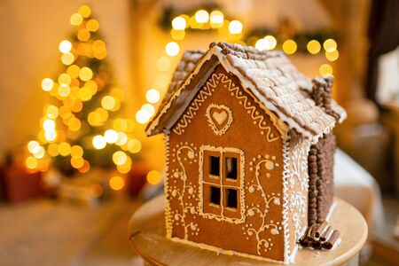 Gingerbread house, concept holiday of Christmas and Happy new year. Defocused lights of Christmas tree. Morning in the bright living room. Holiday mood. Stock Photo