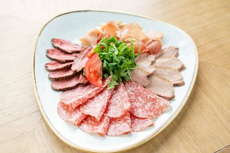 Meat plate, delicacy and Anantipasto. Salami, roast beef, Parma ham, smoked duck breast. Restaurant menu. Stock Photo