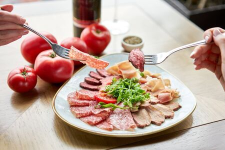 Close-up of Meat on a fork. Meat plate, delicacy and Anantipasto. Salami, roast beef, Parma ham, smoked duck breast. Restaurant menu. Stock Photo