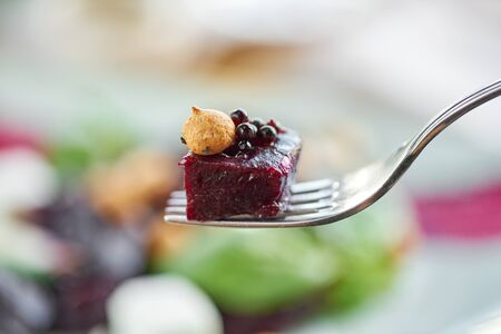 Close-up of a piece of beetroot on a fork. Healthy diet food. Italian salad with beetroot, basil leaves and cheese feta, with oil and small profiteroles. Imagens