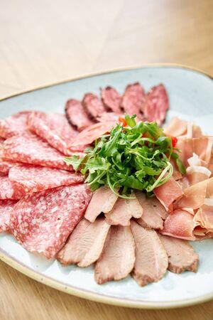 Closeup Meat plate, delicacy and Anantipasto. Salami, roast beef, Parma ham, smoked duck breast. Restaurant menu.