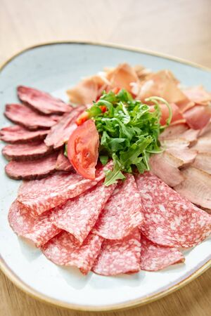 Closeup Meat plate, delicacy and Anantipasto. Salami, roast beef, Parma ham, smoked duck breast. Restaurant menu.