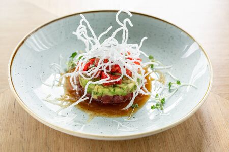 Tartar with tuna in the restaurant. Variety of dishes on the table. Italian cuisine.