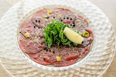 Beef carpaccio with balsamic caviar and Parmesan cheese on wooden table background. Restaurant menu, natural and organic food concept