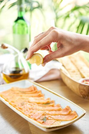 Woman squeeze the juice of a lemon on salted and smoked salmon or trout fillet. Thin slices of red fish with lemon close up. Restaurant menu.
