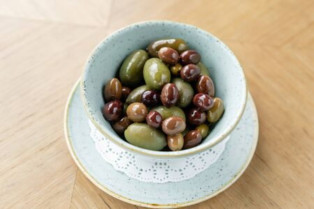 Olives in homemade marinade with herbs. Bowl black and green olives.