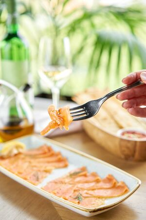 Closeup of salted and smoked salmon or trout fillet on a fork . Thin slices of red fish with lemon close up. Restaurant menu
