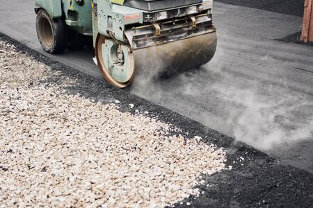 Asphalt Compactors is carrying out road repair work. Laying new asphalt. Large heavy machinery. Construction of a new asphalt road.