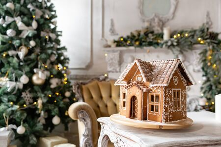 Postcard gingerbread house. Defocused lights of Christmas tree. Holiday mood. Christmas and Happy new year.