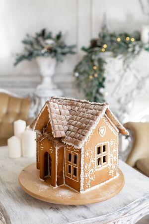 Casa di pan di zenzero da cartolina. Luci sfocate dell'albero di Natale. Umore di vacanza. Natale e felice anno nuovo.