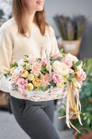 Blumenarrangement im Weidenkorb. Schöner Blumenstrauß gemischter Blumen in der Frauenhand. Blumenladenkonzept. Schöner frischer Strauß. Blumenlieferung