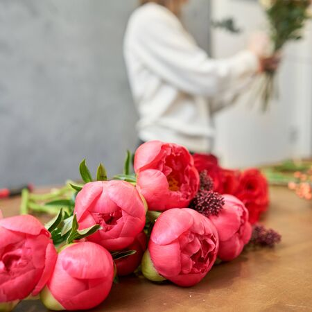 Step by step florist woman creates red beautiful bouquet of mixed flowers. Handsome fresh bunch. Education, master class and floristry courses. Flowers delivery. European floral shop concept
