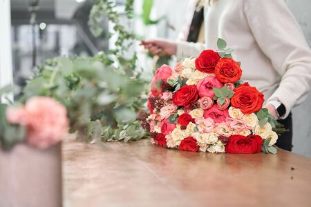 European floral shop concept. Florist woman creates red beautiful bouquet of mixed flowers. Handsome fresh bunch. Education, master class and floristry courses. Flowers delivery