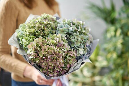 Bouquet of green flower. Beautiful hydrangea flowers in womans hands. the work of the florist at a flower shop. Fresh cut flower Zdjęcie Seryjne
