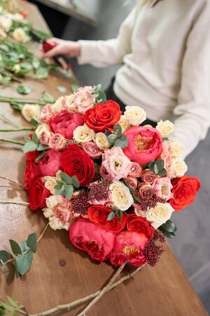 European floral shop concept. Florist woman creates red beautiful bouquet of mixed flowers. Handsome fresh bunch. Education, master class and floristry courses. Flowers delivery.