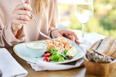 Grillowane krewetki argentyńskie z sosem mango-jalapeno. Obiad w restauracji, kobieta je pyszne i zdrowe jedzenie. Pyszne krewetki ze świeżych owoców morza ze świeżymi warzywami i limonką. Kremowy sos